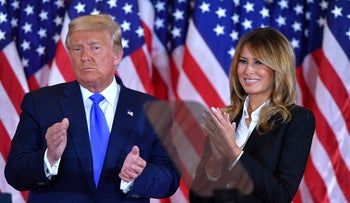 Donald Trump claps alongside Melania Trump after speaking in the East Room of the White House in Washington, D.C., early on November 4, 2020.
