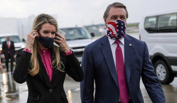 U.S. Senators Kelly Loeffler and David Perdue wearing protective face masks as they walk together at Hartsfield-Jackson Atlanta International Airport following the arrival of U.S. President Donald Trump in Atlanta, July 15, 2020.