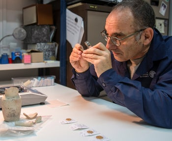 Dr. Robert Kool of the Israel Antiquities Authority examining four gold coins, which date from the late 940s to the 970s C.E. and were unearthed in the Western Wall Plaza of Jerusalem's Old City, October 2020