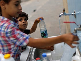 Palestinian children fill bottles with water from public taps during a lockdown amid the coronavirus disease (COVID-19) outbreak, in Jabalia refugee camp in the northern Gaza Strip September 10, 2020.