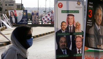 A woman walks past posters of candidates, ahead of parliamentary elections which will be held on November 10, in Amman, Jordan, November 3, 2020.