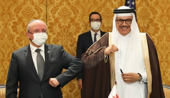 Israel's national security adviser, Meir Ben-Shabbat, left, bumps elbows with Bahrain's Foreign Minister Abdullatif al-Zayani after signing an agreement in Manama, Bahrain, October 18, 2020.