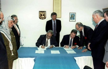Dennis Ross, center, looks on as Saeb Erekat, left, the chief Palestinian negotiator, and Dan Shomron, the chief Israeli negotiator, initial the documents about Israeli troop redeployment in the West Bank city of Hebron, early January 15.