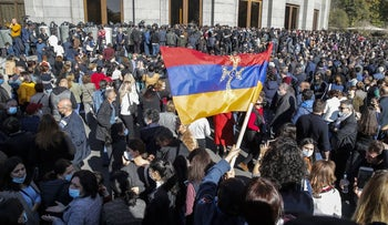 Protesters wave an Armenian national flag during a protest against an agreement to halt fighting over the Nagorno-Karabakh region, in Yerevan, Armenia, November 11, 2020.