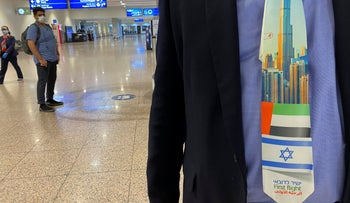 An Israeli tourist wears a souvenir tie with a first flight sign and the flags of Israel and the UAE after landing at Dubai Airport, in the United Arab Emirates, November 8, 2020.