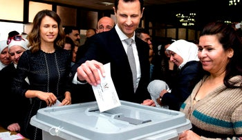 Syrian President Bashar Assad casting his ballot in parliamentary elections, as his wife Asma, left, stands next to him, in Damascus, Syria, April 13, 2016.