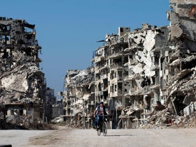 A Syrian boy rides a bicycle through a devastated part of the old city of Homs, Syria, February 26, 2016.