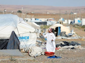 A displaced Iraqi man dismantles his tent as he prepares to be evacuated, at Hammam Al-Alil camp, south of Mosul, Iraq, November 10, 2020.