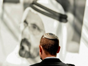 A member of Israeli high-tech delegation stands in front of a poster of Dubai's ruler Sheikh Mohammed bin Rashid al-Maktoum during a meeting with Emirati counterparts in Dubai, October 27, 2020.