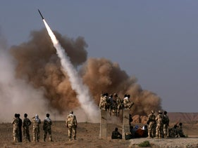 Iranian revolutionary Guards personnel watch the launch of a Zelzal missile during military maneuvers outside the city of Qom, Iran, June 28, 2011