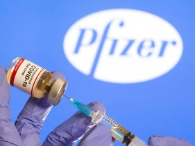 "A woman holds a small bottle labeled with a ""Coronavirus COVID-19 Vaccine"" sticker and a medical syringe in front of displayed Pfizer logo in this illustration taken, October 30, 2020."