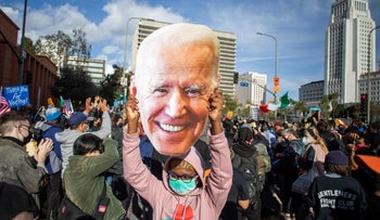 A woman holds a Joe Biden mask as people march in Los Angeles, November 7, 2020.