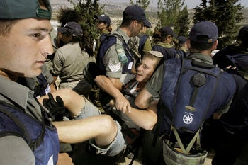 Soldiers forcibly remove a settler during the evacuation of Sa-Nur in 2005.