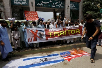Supporters of the Palestine Foundation Pakistan chant slogans burn the U.S. and Israeli flags to condemn the diplomatic agreement between the UAE and Israel. Karachi, Pakistan, August 21, 2020