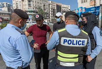 Palestinian police officers issue a ticket to a pedestrian who is not wearing a mask, in the West Bank city of Ramallah, October 21, 2020.