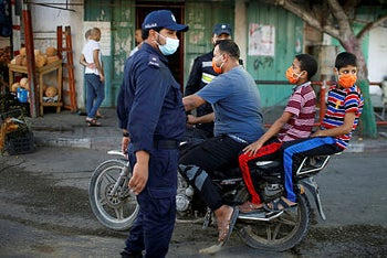 A Palestinian man with his children wearing protective face masks rides his motorcycle by police officers in Gaza September 22, 2020.