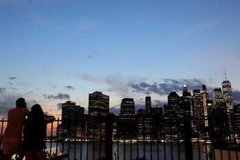 People look toward the skyline of downtown Manhattan from Brooklyn, New York City, U.S., August 14, 2020.