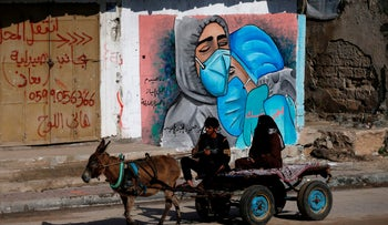 A Palestinian man and his wife ride a donkey cart past street art showing doctors mask-clad due to the coronavirus pandemic in the Nusseirat refugee camp in the central Gaza Strip, November 16, 2020.