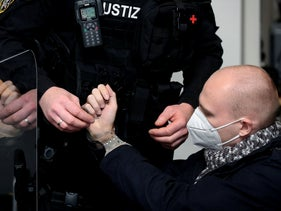 Stephan Balliet, accused of shooting dead two people at a synagogue in Halle, is taken off the handcuffs before the start of the 21th day of his trial in Magdeburg, Germany, November 18, 2020.