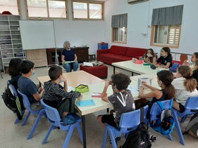Children attending their alternative school with a volunteer teacher at Kibbutz Gazit.