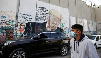 A Palestinian youth walks past an anti-Trump mural which was painted on a section of the Israeli barrier, in Bethlehem, the West Bank, November 2, 2020.