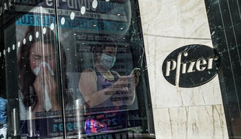 An ad for COVID-19 testing reflects on glass at a bus stop, as pedestrians walk past Pfizer world headquarters in New York, November 9, 2020.