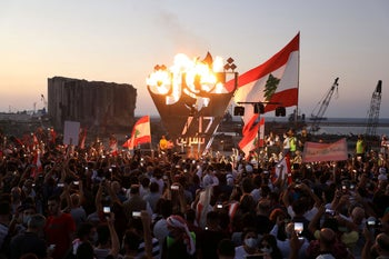 """Anti-government demonstrators spelling out the word """"revolution"""" as Lebanese mark one year since the start of nation-wide protests, near Beirut's port, Lebanon October 17, 2020"""