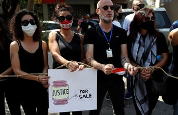 Lebanese anti-government activists protest outside a Lebanese court, as they demanding the improving judicial independence, in Beirut, Lebanon, Wednesday, June 17, 2020.