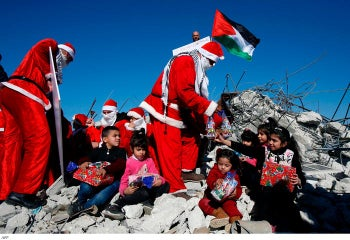 Palestinians wearing Christmas costumes distribute gifts to children seated atop the rubble of a demolished house in Bethlehem, December 23, 2019
