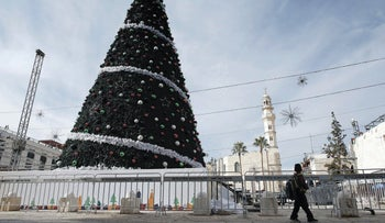 A boy walking past a Christmas tree at Bethlehem's Manger Square near the Church of the Nativity, revered as the site of Jesus Christ's birth, December 16, 2015