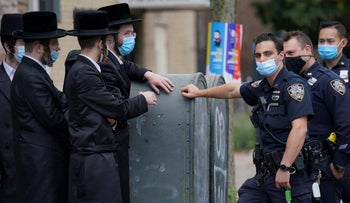 Members of the Orthodox Jewish community speak with NYPD officers, in the Borough Park neighborhood of the Brooklyn borough of New York, Wednesday, October 7, 2020.