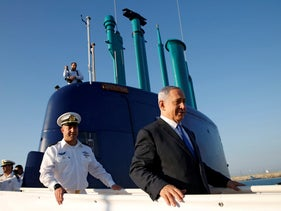 Israeli Prime Minister Benjamin Netanyahu (R) walks on the Rahav, the fifth submarine in the fleet, after it arrived in the Haifa port, January 12, 2016.