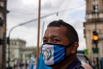 A street vendor wearing a protective face mask with the colors of the Guatemalan flag, as a precaution against the spread of the coronavirus, in Guatemala City, September 14, 2020.