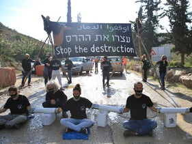 Activists chained to one another during a protest against Israeli construction plans on a unique West Bank ecosystem, November 22, 2020.