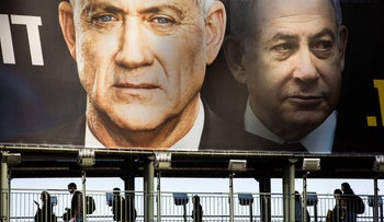 People walk on a bridge under an election campaign billboard for the Kahol Lavan party led by Benny Gantz, left, in Ramat Gan, Israel, February, 18, 2020.