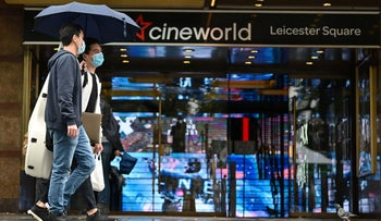 People walk past a Cineworld cinema in Leicester Square in central London on October 4, 2020.
