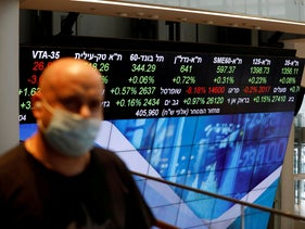 A man wearing a face mask stands near an electronic board displaying market data at the Tel Aviv Stock Exchange, in Tel Aviv, November 4, 2020.