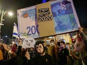 At an anti-Netanyahu demonstration near the prime minister's official residence, protesters raise an enlarged 200 shekel bill, on which the words '2020 state budget' appear, Jerusalem, August 8, 2020.