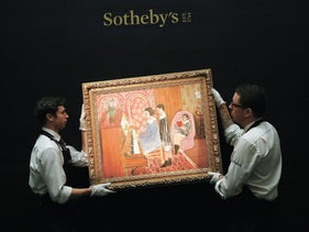 Gallery assistants pose with the painting 'La Lecon de piano' by Henri Matisse at Sotheby's in London.