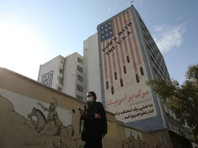 woman walks as an anti-America image is seen on a building in Tehran, Iran November 8, 2020