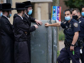 Members of the Orthodox Jewish community speak with NYPD officers, October 7, 2020, in the Borough Park neighborhood of Brooklyn.