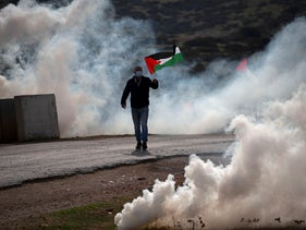 A demonstrator carrying a Palestinian flag runs through a cloud of tear gas fired by Israeli forces during clashes, in the Jordan Valley of the West Bank, November 24, 2020.