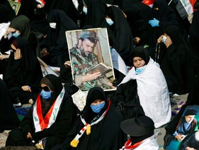 Supporters of Iraqi Shi'ite cleric Moqtada al-Sadr hold a picture of him during a rally in support of al-Sadr in Baghdad, Iraq November 27, 2020.