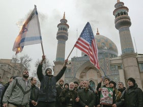 Iranians burn an Israeli and U.S> flag during an anti-United States protest in Tehran, Iran, January 4, 2020.