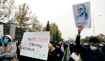 """At a protest in Tehran against the killing of Mohsen Fakhrizadeh, a sign reads """"Revenge means that Tel Aviv will burn with fire,"""" alongside a picture of the slain scientist, Iran, November 28, 2020."""