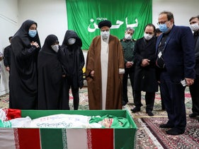 Iran's Judiciary Chief Ayatollah Ebrahim Raisi pays his respect to the body of slain scientist Mohsen Fakhrizadeh among his family, in Tehran, Iran, Saturday, Nov. 28, 2020.