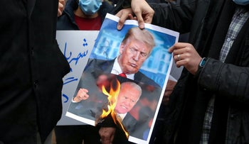 Students of Iran's Basij paramilitary force burn posters depicting Donald Trump and Joe Biden, during a rally in front of the foreign ministry in Tehran, on November 28, 2020,