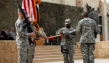 Command Sgt. Major Joseph R. Allen, left, and Army Gen. Lloyd Austin, right, Commander of US Forces Iraq, encase the US Forces Iraq colors during a ceremony in Baghdad, Iraq, Thursday, Dec., 15, 2011