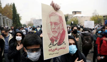 A protester holds a picture of Mohsen Fakhrizadeh, Iran's top nuclear scientist, during a demonstration against his killing in Tehran, Iran, November 28, 2020.