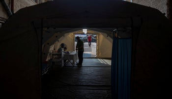 A Palestinian medic checks a person's temperature to screen for coronavirus symptoms, inside a temporary tent at the entrance al-Quds Hospital, Gaza City, September 7, 2020.